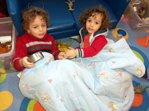 Children relaxing under blanket